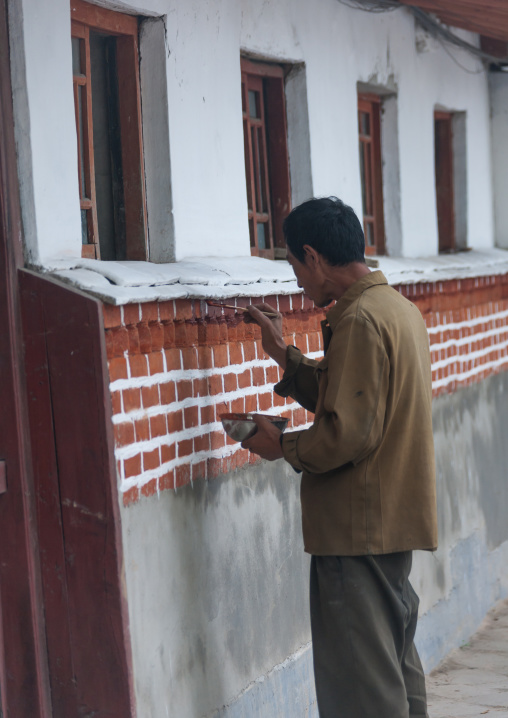 North Korean man painting a house in the old town, North Hwanghae Province, Kaesong, North Korea
