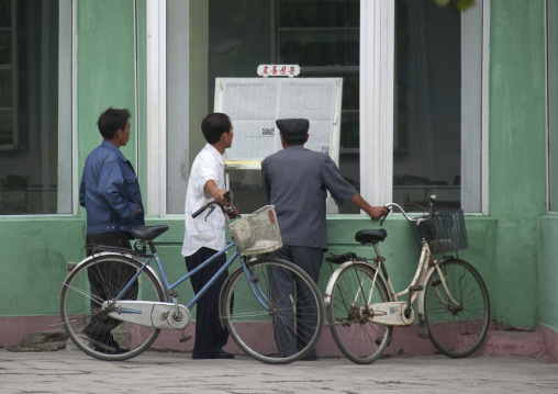 North Korean people reading the offical state newspaper in the street, North Hwanghae Province, Kaesong, North Korea