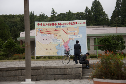 North Korean men in front of the map of the last Kim Jong il trips in train, North Hwanghae Province, Kaesong, North Korea