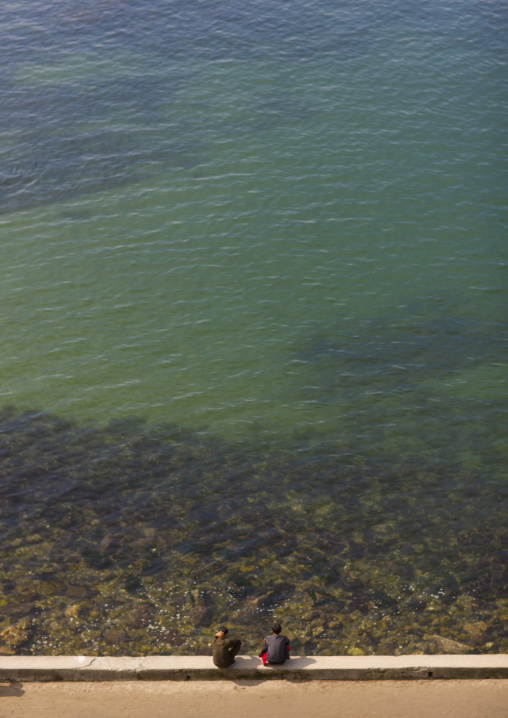 Two North Korean men sitting in front of clear water, Kangwon Province, Wonsan, North Korea