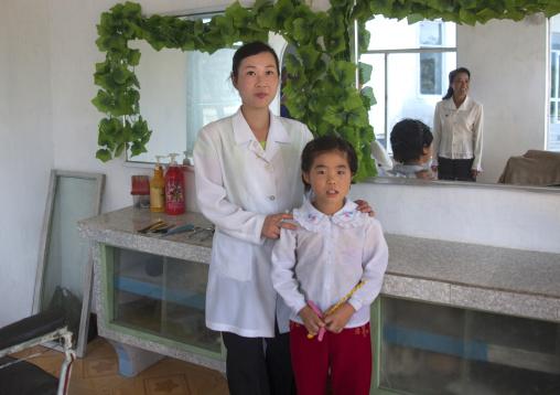 North Korean haidresser with a child, South Pyongan Province, Chonsam Cooperative Farm, North Korea