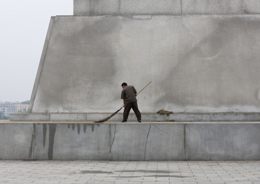 North Korean man with a broom at the bottom of the Juche tower, Pyongan Province, Pyongyang, North Korea