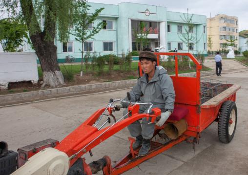 North Korean man driving a tractor in a village, South Pyongan Province, Chongsan-ri Cooperative Farm, North Korea