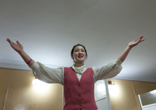 North Korean waitress in a restaurant singing for the tourists, Pyongan Province, Pyongyang, North Korea