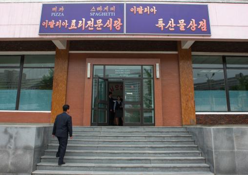 North Korean man entering a pizzeria restaurant, Pyongan Province, Pyongyang, North Korea