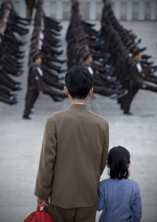Father and daughter watching North Korean army parade on Kim il Sung square, Pyongan Province, Pyongyang, North Korea