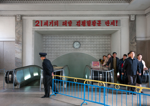 North Korean people coming out from a subway station with the slogan saying long live general Kim Jong-il the 21st century sun, Pyongan Province, Pyongyang, North Korea