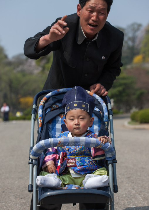Portrait of a North Korean father with his one year old son in a baby-buggy, Pyongan Province, Pyongyang, North Korea