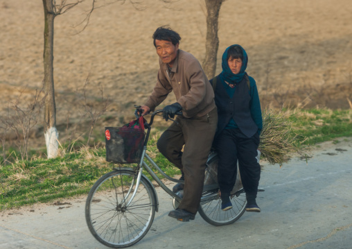 North Korean couple riding a bicycle in the countryside, Kangwon Province, Chonsam Cooperative Farm, North Korea