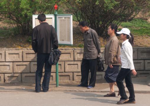 North Korean people reading the newspaper displayed in the street, Pyongan Province, Pyongyang, North Korea