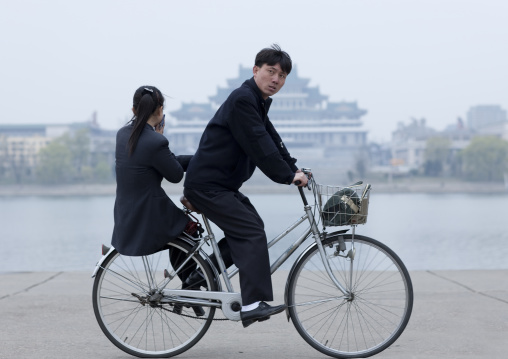 North Korean couple riding a bicycle on Kim il Sung square, Pyongan Province, Pyongyang, North Korea