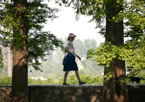 North Korean teenage girl walking in a park, North Hwanghae Province, Kaesong, North Korea
