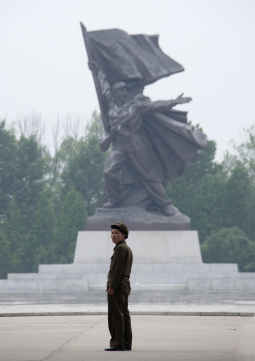 North Korean man standing in front of a sioldier statue, Pyongan Province, Pyongyang, North Korea