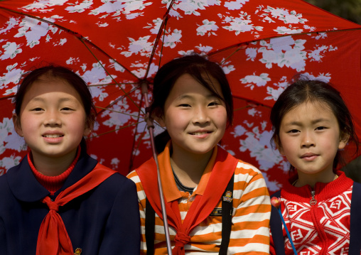 Three North Korean young pioneers under an umbrella, Pyongan Province, Pyongyang, North Korea