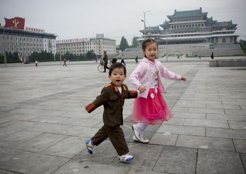North Korean boy dressed in soldier with his sister in choson-ot on Kim il Sung square, Pyongan Province, Pyongyang, North Korea