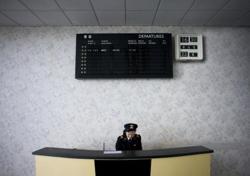 North Korea airport employee in Sunan international airport below the departures billboard, Pyongan Province, Pyongyang, North Korea
