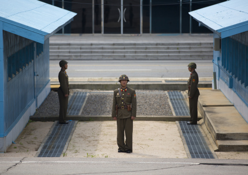 Three North Korean soldiers standing in front of the United Nations conference rooms on the demarcation line in the Demilitarized Zone, North Hwanghae Province, Panmunjom, North Korea