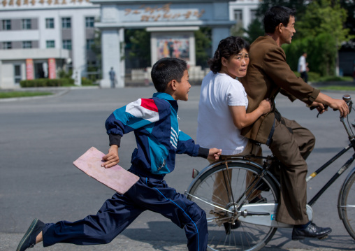 North Korean boy running after a couple riding a bicycle, Pyongan Province, Pyongyang, North Korea