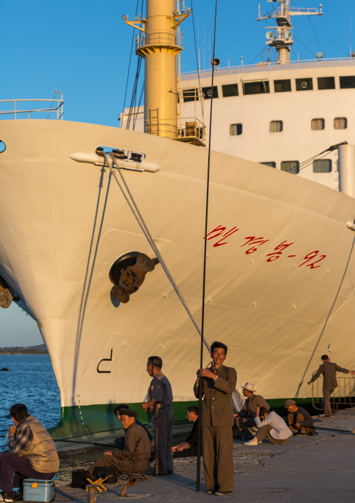 North Korean men fishing in front of a ship in the port, Kangwon Province, Wonsan, North Korea