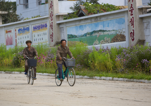 Two North Korean men riding bicycles in a village, South Hamgyong Province, Hamhung, North Korea