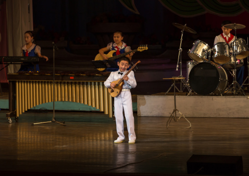 Young North Korean artist playing guitar during a show in Mangyongdae children's palace, Pyongan Province, Pyongyang, North Korea