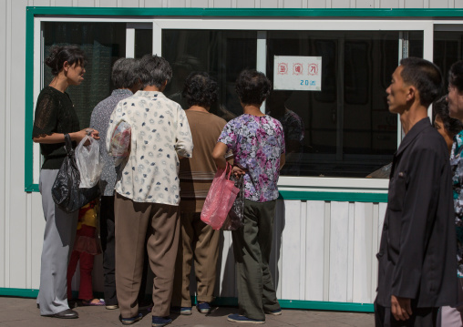 North Korean people queueing to buy some food in a shop in the street, Pyongan Province, Pyongyang, North Korea