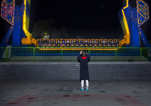North Korean girl taking a picture of a fairground attraction in Kaeson youth park, Pyongan Province, Pyongyang, North Korea