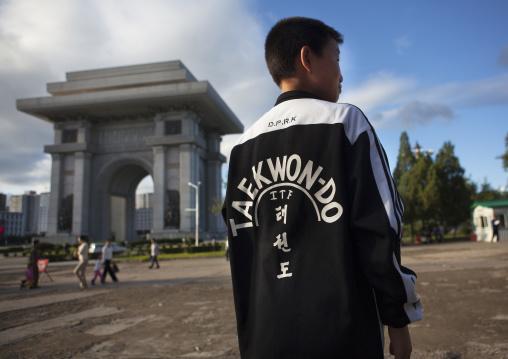 North Korean boy wearing a taekwondo shirt in front of the arch of triumph, Pyongan Province, Pyongyang, North Korea