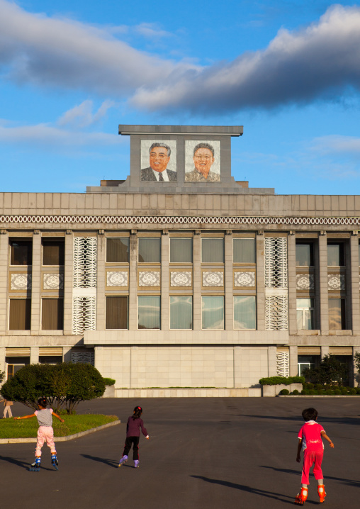 North Korean children roller skating in front of the portraits of the Dear Leaders, Pyongan Province, Pyongyang, North Korea