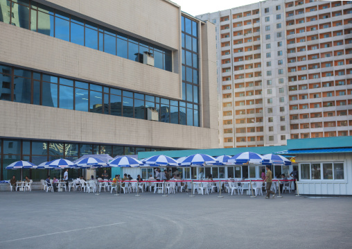 Cafe with umbrellas in the street in the middle of buildings, Pyongan Province, Pyongyang, North Korea