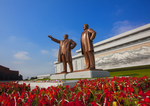 Baskets of flowers in front of the two statues of the Dear Leaders in the Grand monument on Mansu hill, Pyongan Province, Pyongyang, North Korea