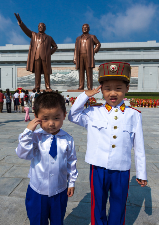 North Korean children saluting like soldiers in front of the statues of the Dear Leaders in Mansudae Grand monument, Pyongan Province, Pyongyang, North Korea