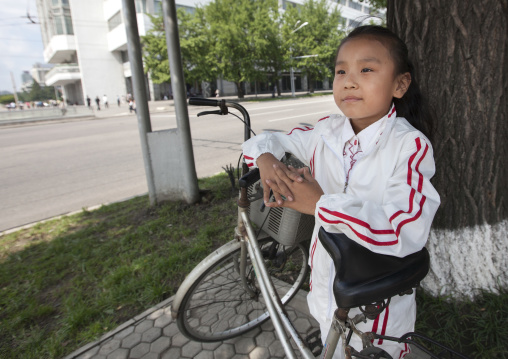 North Korean girl in the street with a bicycle, Pyongan Province, Pyongyang, North Korea