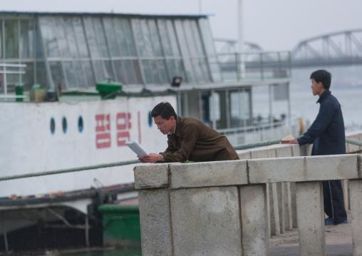 North Korean man reading a newspaper in front of a boat, Pyongan Province, Pyongyang, North Korea