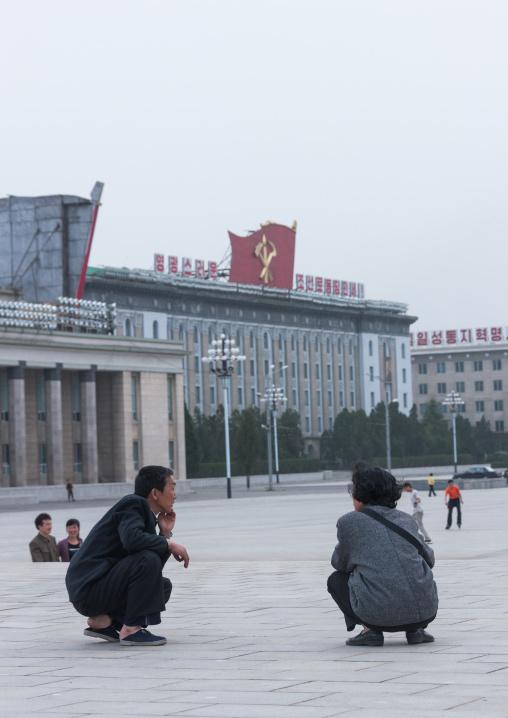 North Korean men squatting on Kim il Sung square, Pyongan Province, Pyongyang, North Korea