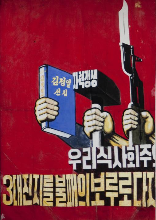 North Korean propaganda billboard with a book a hammer and a gun, Pyongan Province, Pyongyang, North Korea