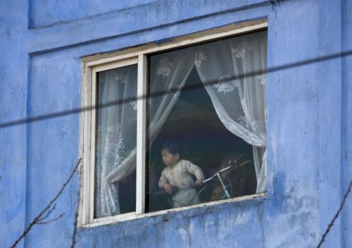 North Korean child looking thru a window, Pyongan Province, Pyongyang, North Korea