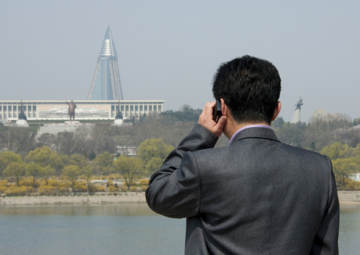 North Korean man calling with his mobile in front of the pyramid-shaped Ryugyong hotel, Pyongan Province, Pyongyang, North Korea