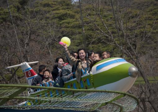 North Korean people having fun on a flying saucer attraction in Taesongsan funfair, Pyongan Province, Pyongyang, North Korea