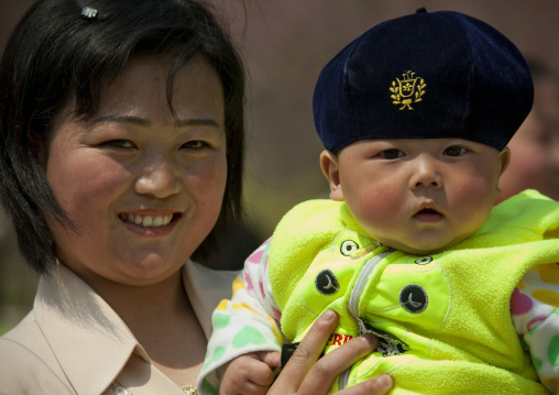 North Korean mother holding her baby who wears a beret in her arms, Pyongan Province, Pyongyang, North Korea