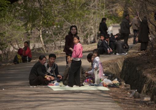 North Korean family having a picnic on a road leading to a park, Pyongan Province, Pyongyang, North Korea
