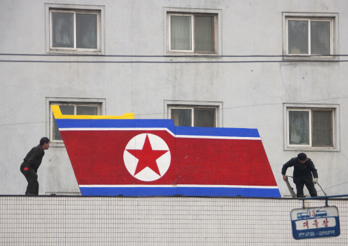 North Korean men setting a giant flag on a building, Pyongan Province, Pyongyang, North Korea
