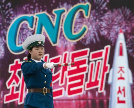 North Korean traffic security officer in blue uniform in front of a propaganda billboard, Pyongan Province, Pyongyang, North Korea