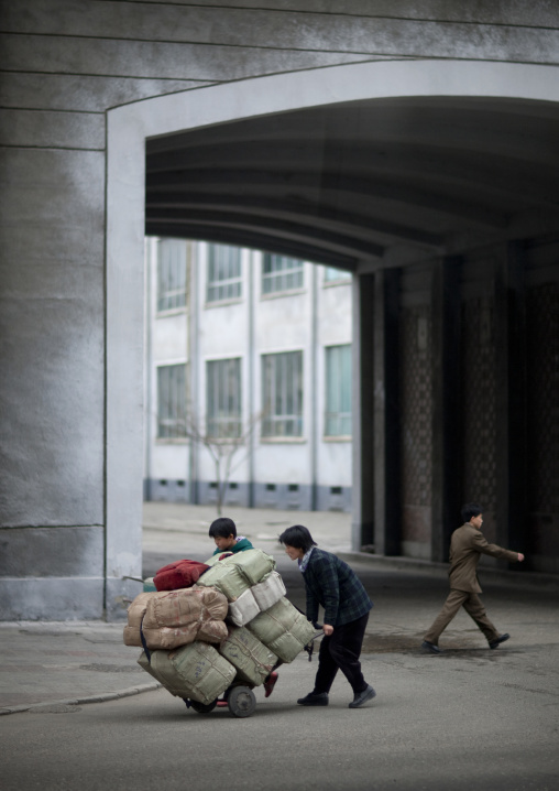 North Korean mother and child pushing a heavy trolley in the city, Pyongan Province, Pyongyang, North Korea
