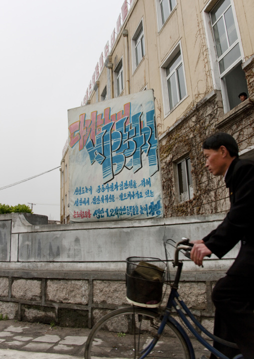 North Korean cyclist passing in front of a propaganda billboard about the great economic development, North Hwanghae Province, Kaesong, North Korea