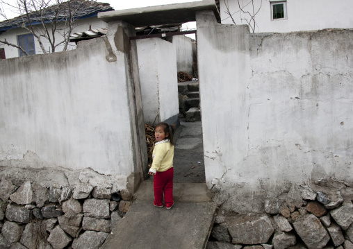 Little North Korean girl at the entrance of her house in the countryside, North Hwanghae Province, Kaesong, North Korea