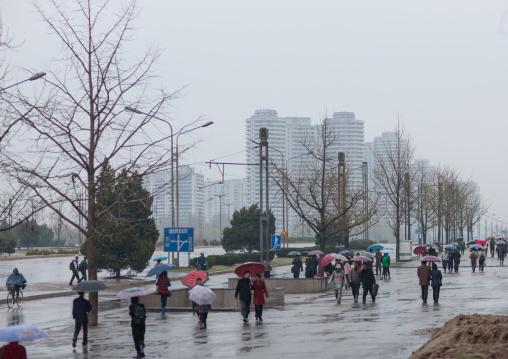 North Korean people walking in the street under the rain, Pyongan Province, Pyongyang, North Korea