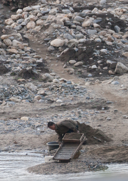 North Korean man panning for gold in a river, Kangwon Province, Wonsan, North Korea