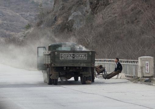 North Korean men repairing a smoking vapor truck on a highway, Kangwon Province, Wonsan, North Korea