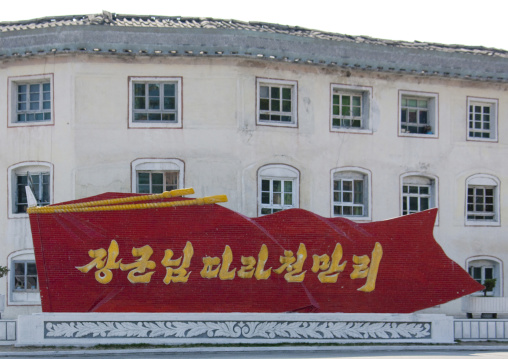 Propaganda slogan on a red billboard in town, Kangwon Province, Wonsan, North Korea